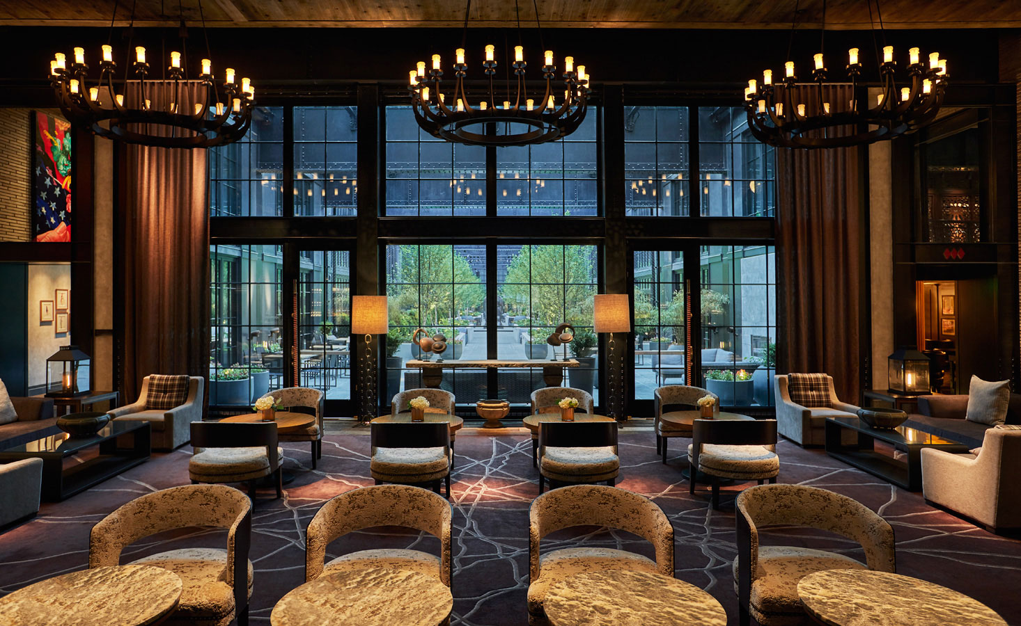 Sophisticated hotel lobby with decorations and large glass windows overseen by hotel asset management services firm, hotelAVE