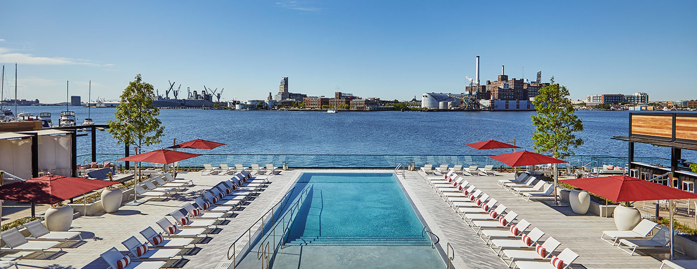 Outdoor hotel pool and lounge area overlooking a harbor, within the portfolio of asset management services firm, hotelAVE